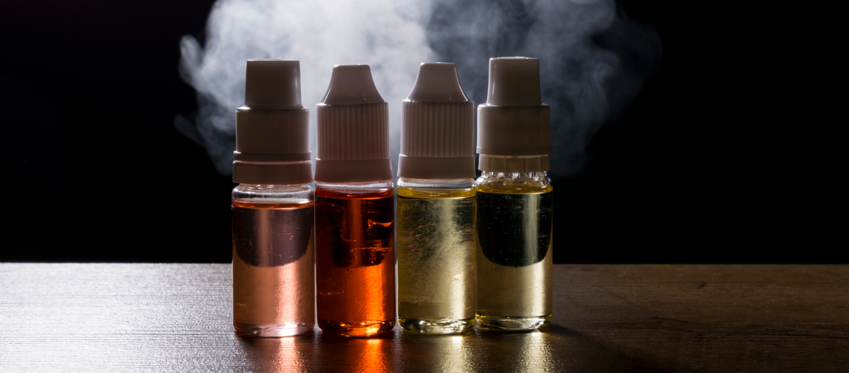 Four different bottles with liquid inside placed in the middle of the table with smoke used for vaping - Best Vaping E Liquids With Flavours