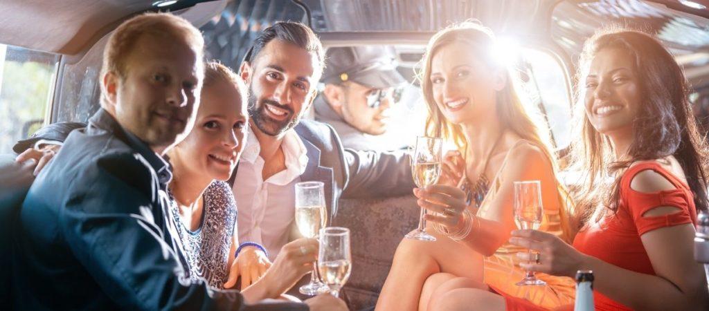 Homens e mulheres em traje informal bebendo champanhe dentro de um carro, indo para uma festa hen