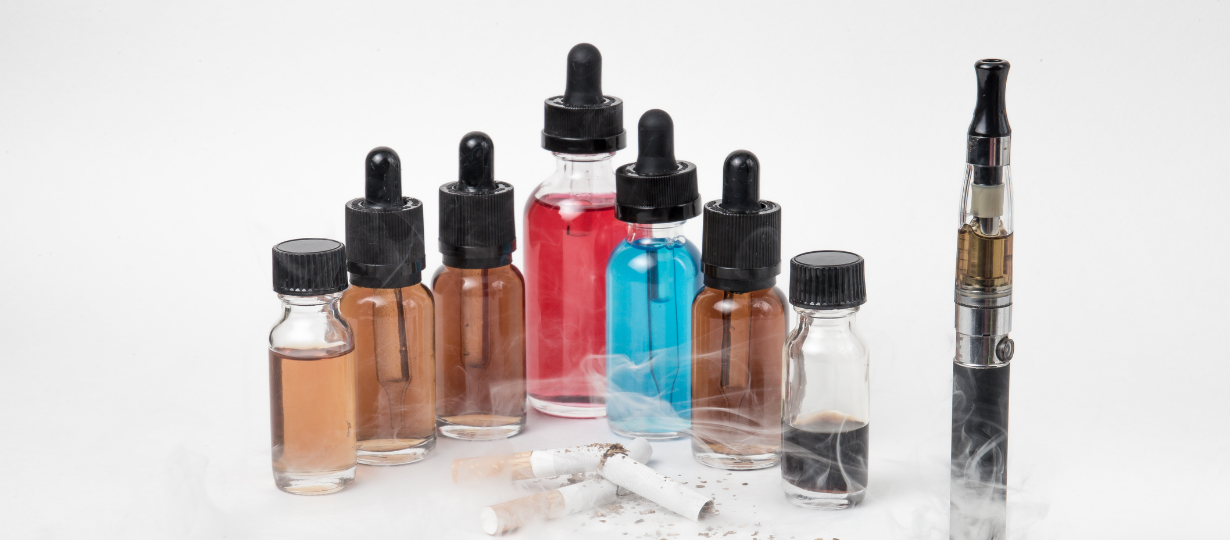 Different eliquid bottles in different colors with cigarette and smoke. Premium Vaping Nicotine Shots used for vaping