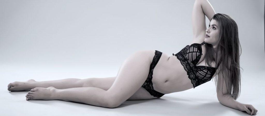 Curvy women wearing black plus sized sexy lingerie in seductive position