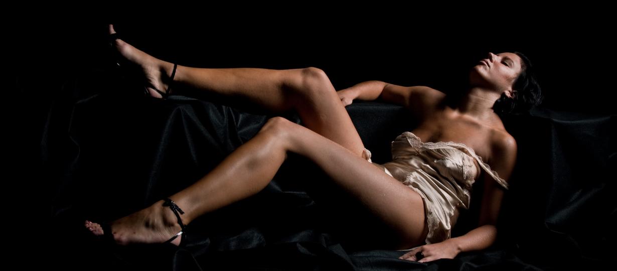 Femme sexy portant des nuisettes blanches révélatrices allongées sur un tissu noir en soie.