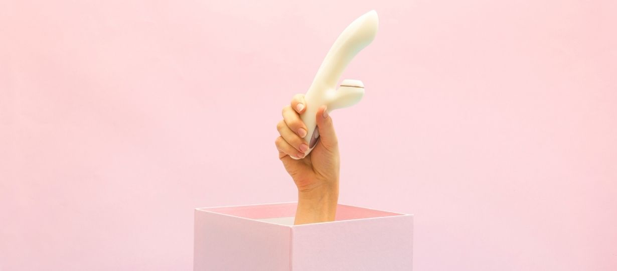 A hand in a box holding a white sex toy with pink background. Naughty branded sex toys for infinite pleasure