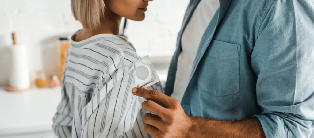 Femme devant un homme qui a un préservatif à la main