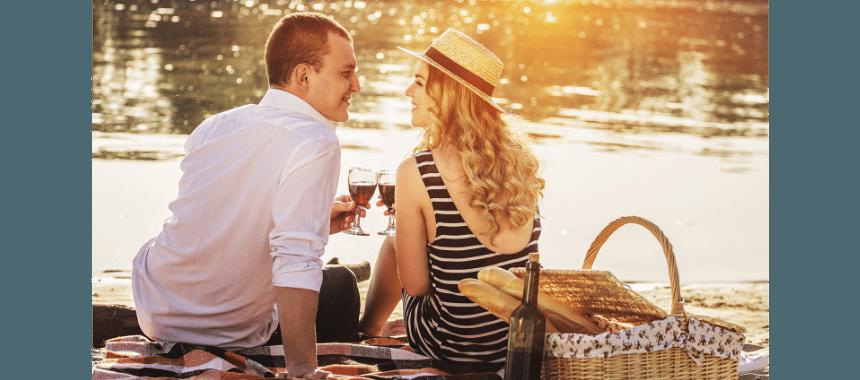 casal sentado perto de um lago, ele está à esquerda, ela à direita, torrando com um copo de vinho, o sol brilha e eles estão sorrindo um para o outro, ele está vestido com uma camisa branca, ela com um vestido preto e usando chapéu, ela é ousada e tem um sorriso muito sexy