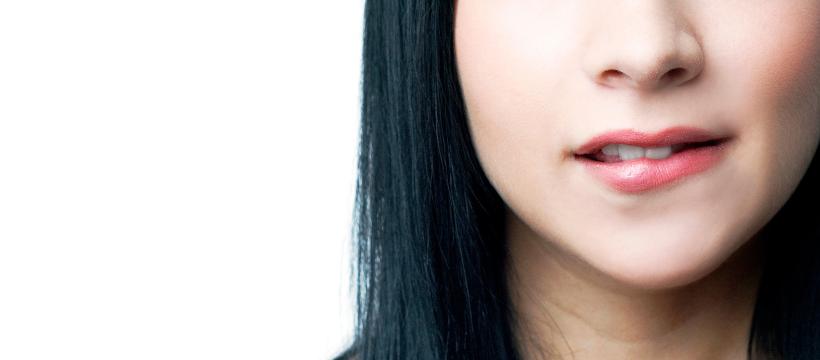 imagem do rosto de uma mulher bonita com cabelo escuro comprido, apenas vendo do nariz ao pescoço, ela está mordendo-a debaixo do lábio, uma expressão muito sexy, esta imagem faz parte do seguinte post: Como atrair e seduzir uma mulher mais nova