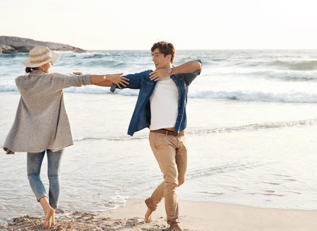 zwei Personen am Strand, links eine Frau mit Blick auf das Meer und die Männer, er schaut zum Strand und zu ihr, sie lächeln sich an, sehen sehr glücklich aus und strecken sich die Arme aus, sie sind beide lässig gekleidet, aber barfuß, das ist das Bild von 'Wie man die beste Lebensweise bekommt'