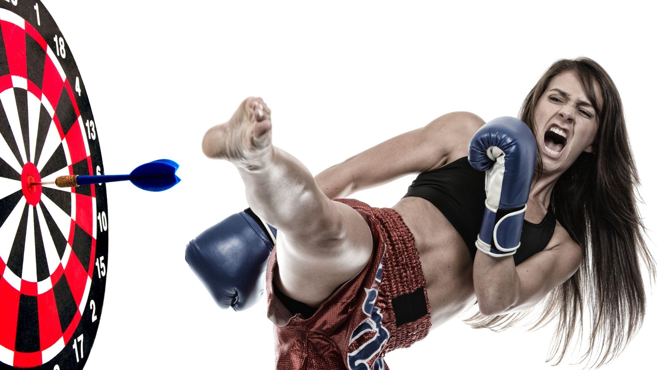 Comment atteindre vos objectifs, Image - Une belle artiste martiale aux cheveux longs, vêtue d'un haut court sans manches sombre et d'un short de sport à carreaux bleu et doublure blanche avec ses gants et position de coup de pied vers un jeu de fléchettes.