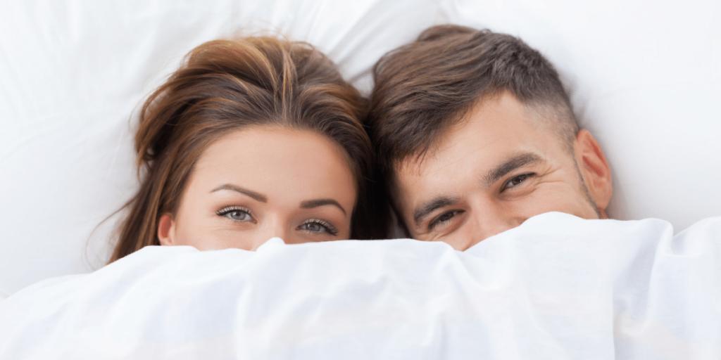 Femme et homme regardant hors d'un lit meublé blanc, ne voyant que du nez vers le haut, semblent tous deux avoir une expression souriante