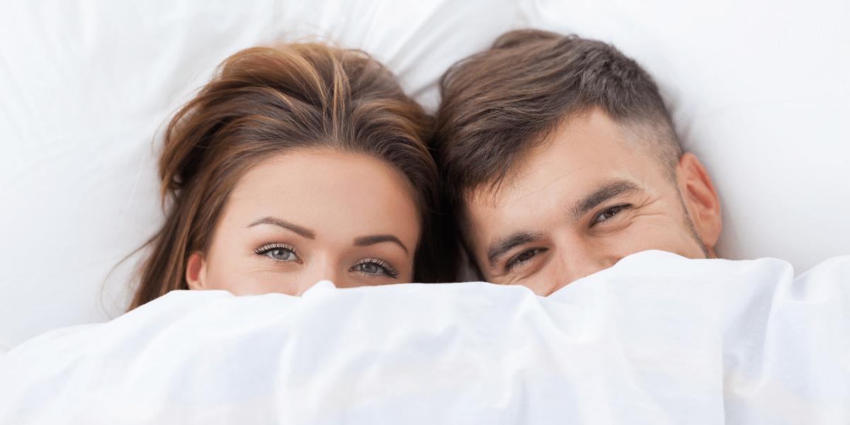 Mulher e homem olhando para fora de uma cama mobilada branca, vendo apenas do nariz para cima, ambos parecem ter uma expressão sorridente