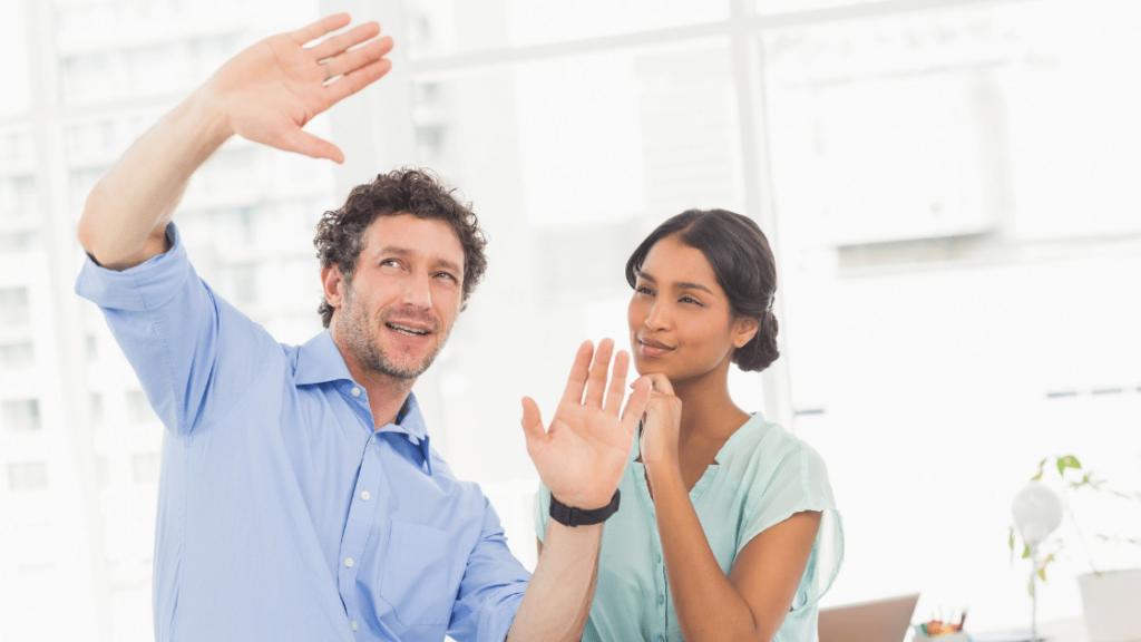 Nutzen Sie die Kraft Ihres Geistes durch Visualisierungsbild – Ein lockiger Mann mit blauem Polo und einer lächelnden Frau. Mann und Frau sprechen und visualisieren Ideen mit Handgesten. Frau trägt eine grüne Bluse mit der linken Hand am Kinn.