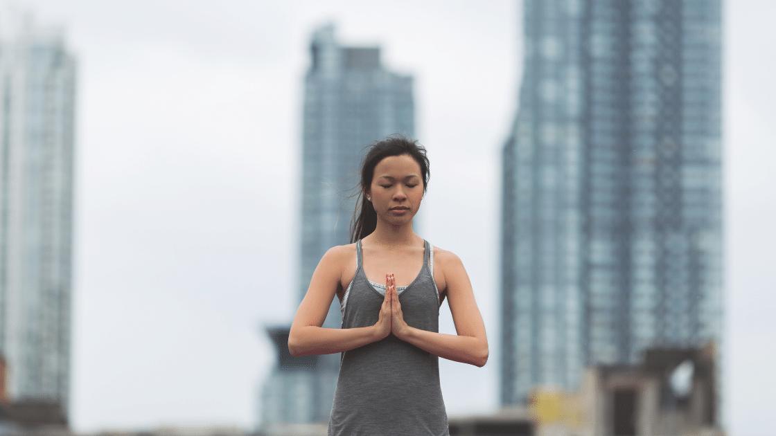 comment avoir une meilleure mise au point, femme portant des manches gris foncé en pose de méditation avec des bâtiments flous en arrière-plan