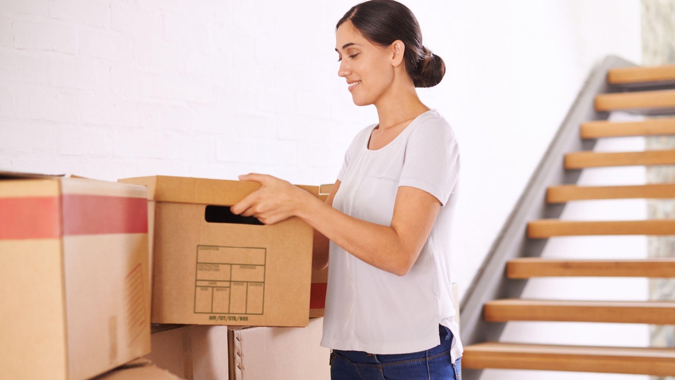 photo d'une femme qui soulève une boîte en carton, comme si c'était pour un déménagement, elle est vêtue d'un jean et d'un t-shirt blanc, elle sourit et a les cheveux attachés, elle est devant un escalier, cette image appartient à l'article intitulé 'Comment recommencer la vie'