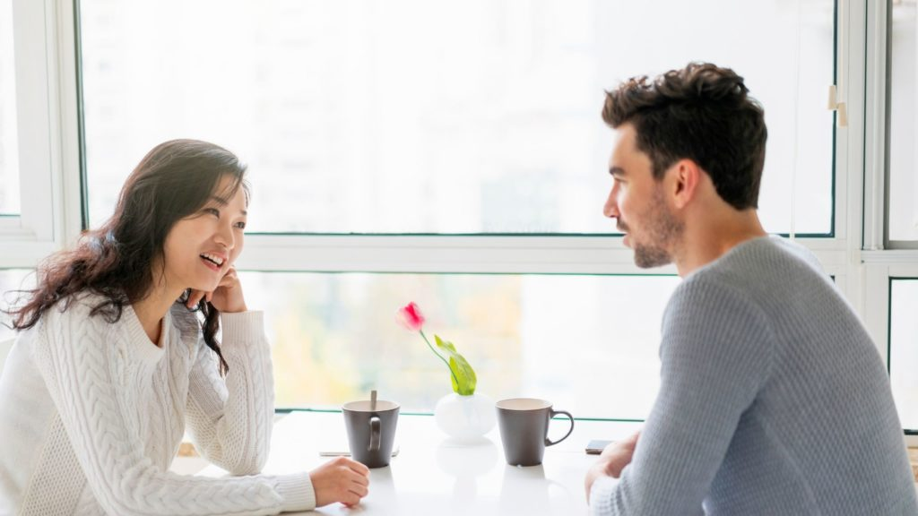 Photo taken inside in front of a window, a couple sitting around a little white table, they are talking to each other, she is sitting on the left with a white pullover, he on the right with a grey pullover, they have a brown mug in front of them, in the middle of the table a vase with a red rose, this photo is part of the article called 'the morning ritual'