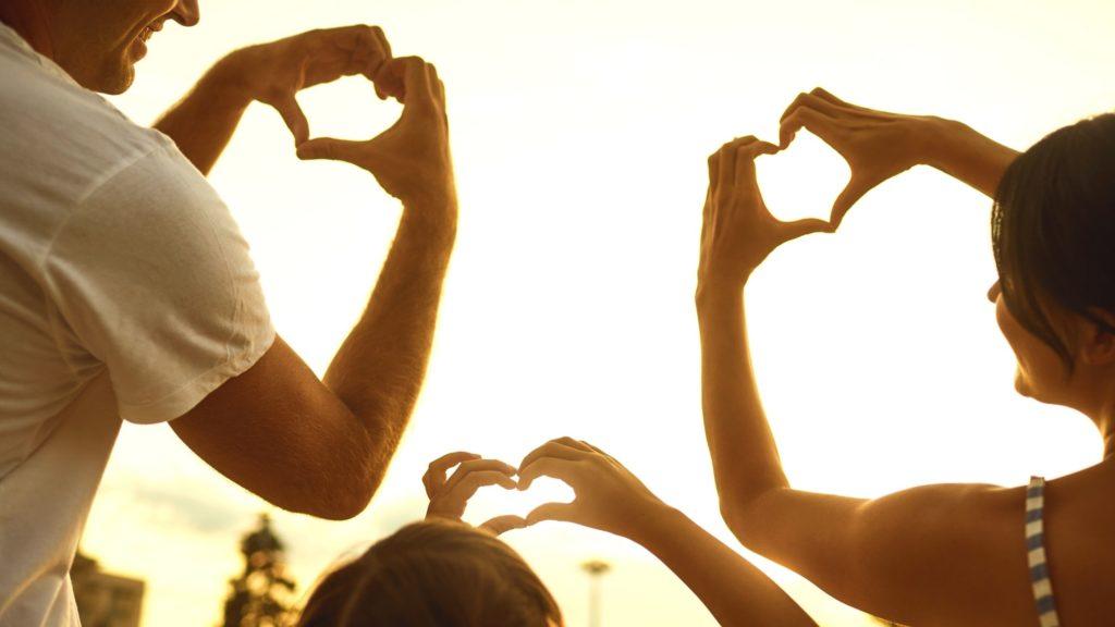 """photo d'une famille prise contre le soleil, de gauche à droite, un homme, un enfant au milieu et une femme à droite, on voit juste le haut du corps, ils font le signe """"coeur"""" avec leurs deux mains et sourient, cette photo fait partie de l'article intitulé """"Conseils pour des habitudes de vie saines et une énergie de style de vie"""""""
