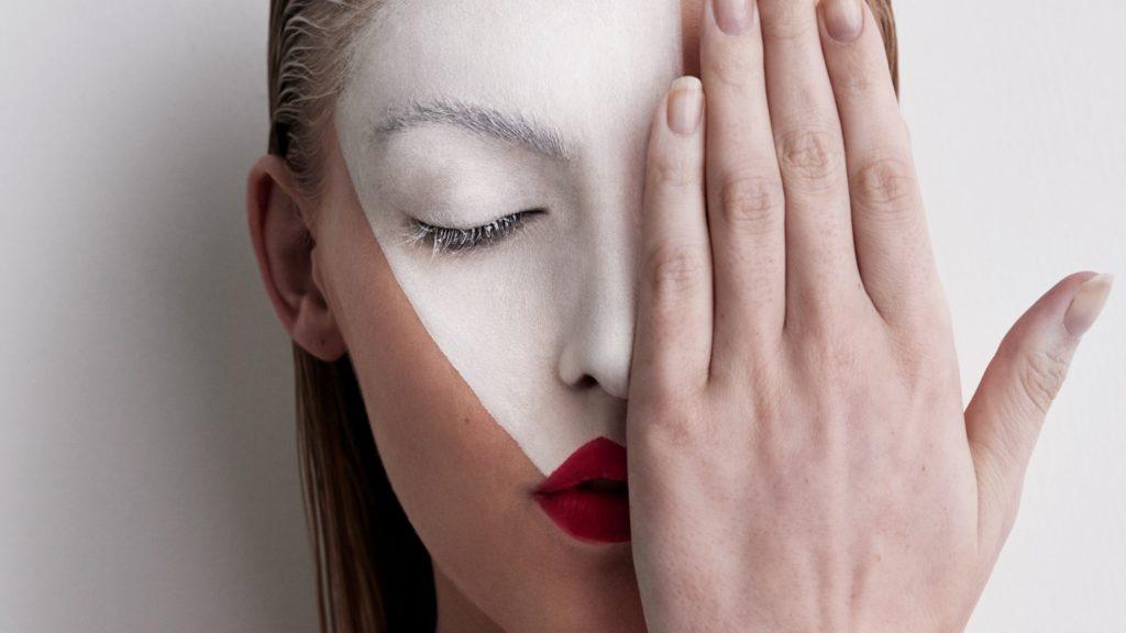 """imagem da cabeça de uma mulher, tem os olhos fechados mas esconde-se com a mão esquerda do lado esquerdo do rosto, os lábios têm batom vermelho e dos lábios na testa tem uma máscara pintada branca, parece bonita e misteriosa, esta imagem faz parte deste artigo chamado """"como superar obstáculos"""""""