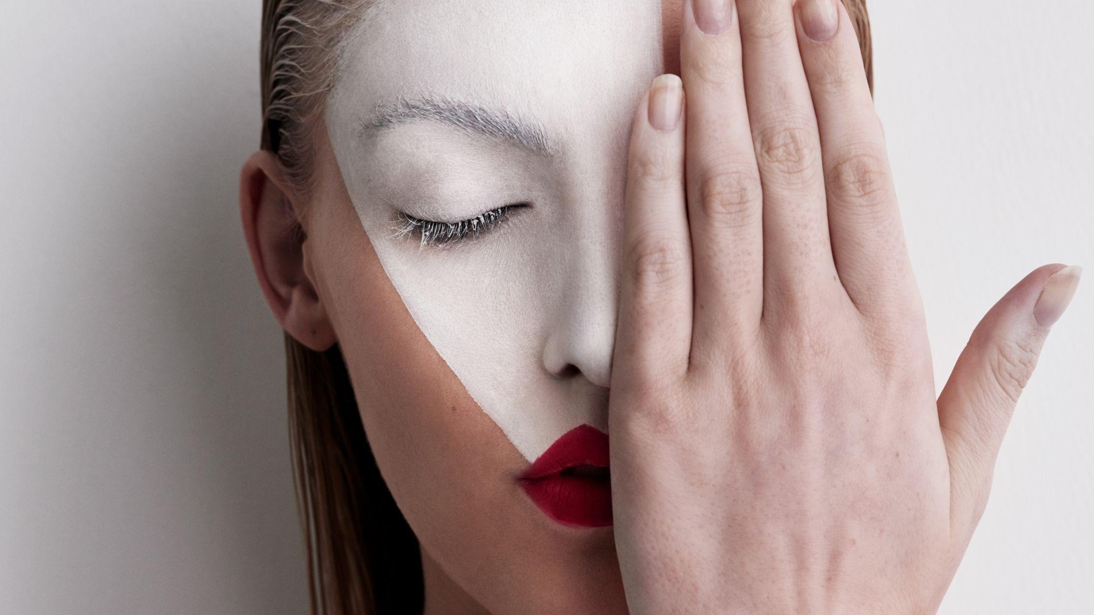 photo d'une tête de femme, elle a les yeux fermés mais cache avec sa main gauche le côté gauche de son visage, ses lèvres ont du rouge à lèvres rouge et des lèvres sur son front, elle a un masque peint en blanc, elle est belle et mystérieuse, cette image fait partie de cet article intitulé « comment surmonter les obstacles »