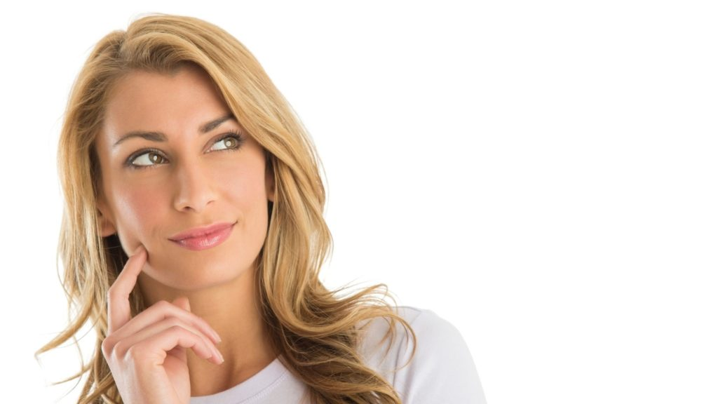 photo showing from the neck up a beautiful blond woman with curly hair, she is touching her face with her index finger and looking to her left, the background is white, she has a light smiling without showing her teeth, she is dressed with a white t-shirt but we only see the top, she has a thinking expression, her lips have rose lipstick and are reflecting the light, this image is part of the article named 'What mindfulness is and how to level up mind'