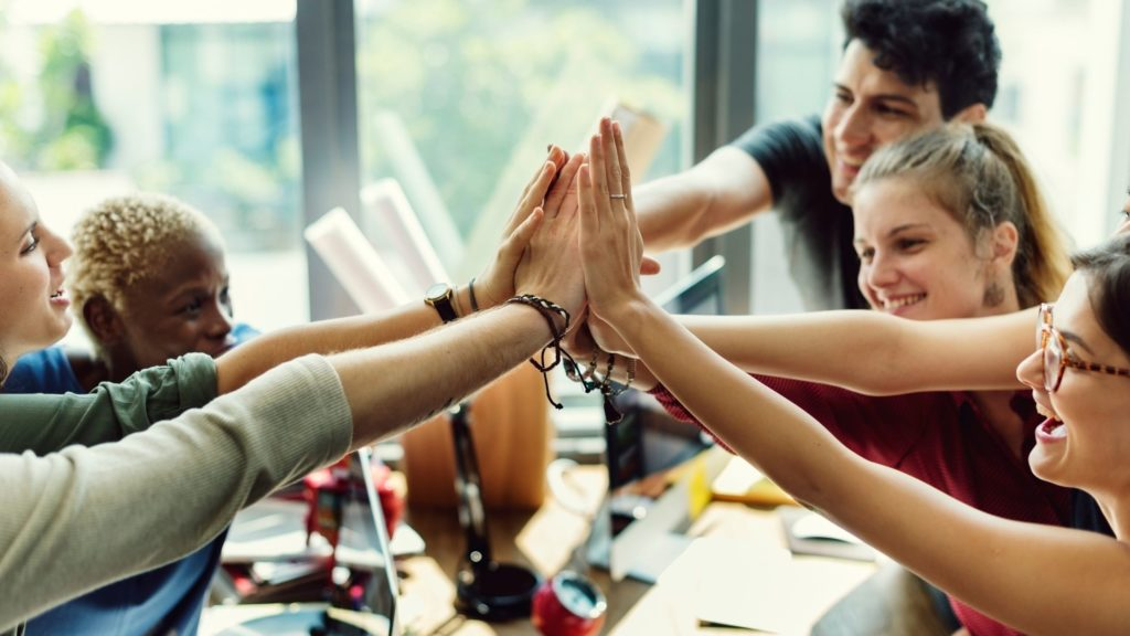 Success Principles Resources, image of 5 different people with their hands raised smiling at each other looking happy and accomplished. There's a boy wearing black, a blonde girl wearing red long sleeves, another girl wearing glasses, a girl wearing green and another woman wearing blue.