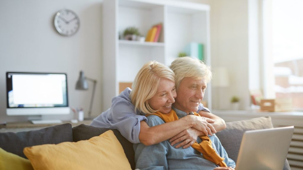 The senior man is wearing blue long sleeves while holding his laptop. He is smiling while the senior lady is hugging the man from the back. At the back of the woman is a Mac computer, a wall clock, a table lamp and a book shelf. This image is part of the article named 'Work from home for seniors'