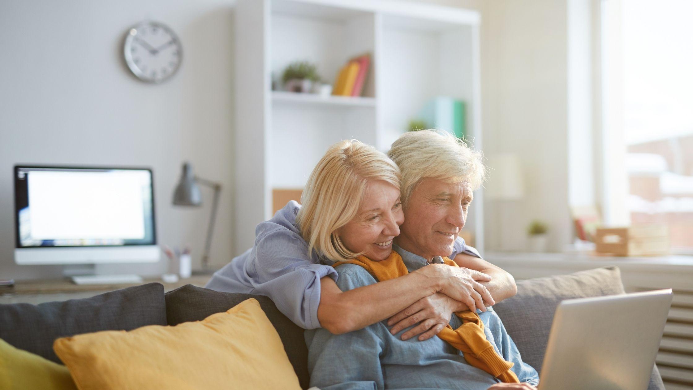 """O homem mais velho está a usar mangas compridas azuis enquanto segura o portátil. Ele está a sorrir enquanto a senhora sénior está a abraçar o homem pelas costas. Na parte de trás da mulher está um computador Mac, um relógio de parede, um candeeiro de mesa e uma prateleira de livros. Esta imagem faz parte do artigo chamado """"Trabalho a partir de casa para idosos"""""""