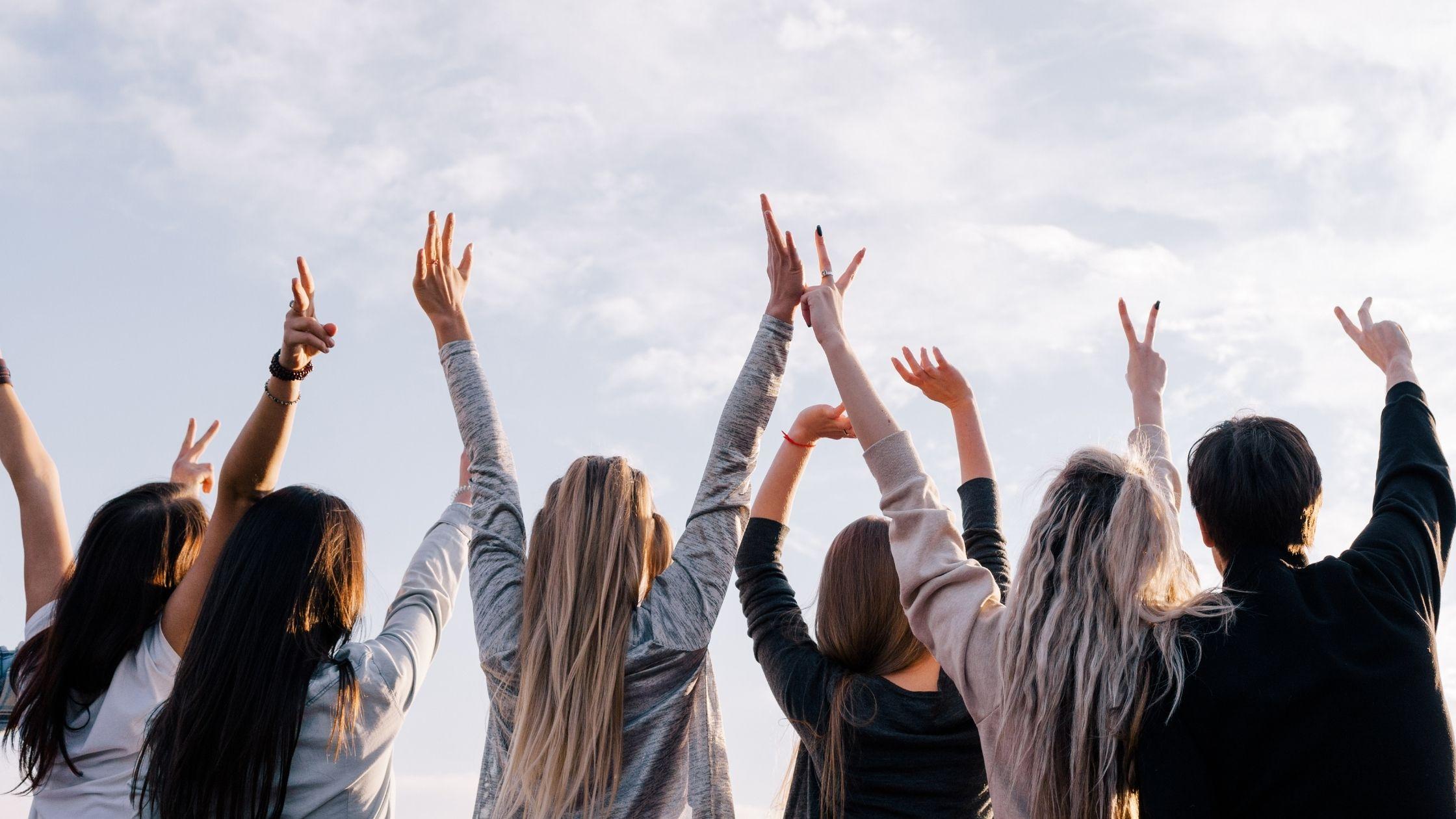 """foto de um grupo de jovens, tirados de costas, todos eles erguendo os dois braços contra o céu, parece que estão a ser gratos, isto faz parte do artigo chamado """"como melhorar as capacidades de auto-desenvolvimento"""""""
