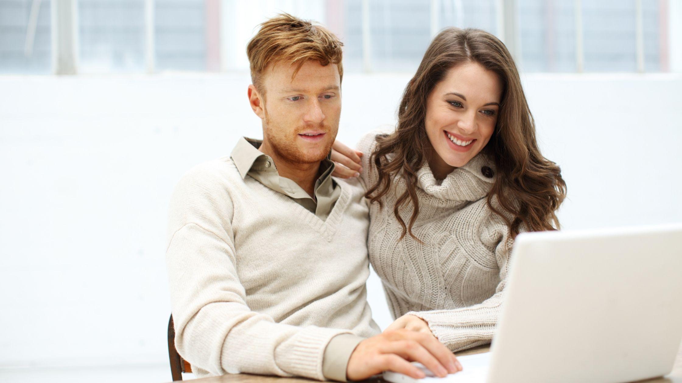 Como aumentar as vendas online. Imagem de um homem e mulher olhando para um portátil com sorrisos. O cara vestindo camisola branca com cabelo loiro enquanto a mulher com cabelo comprido e bonito de curvas vestindo camisola de gola alta cinzenta.