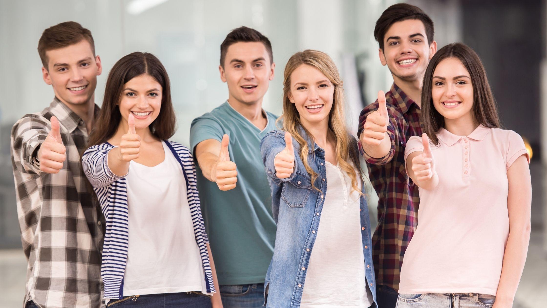 A imagem do artigo 'Como aumentar a auto-confiança' mostra 6 pessoas. Há 3 raparigas e 3 rapazes a mostrar um gesto de sucesso enquanto fazem o sinal dos polegares para cima.