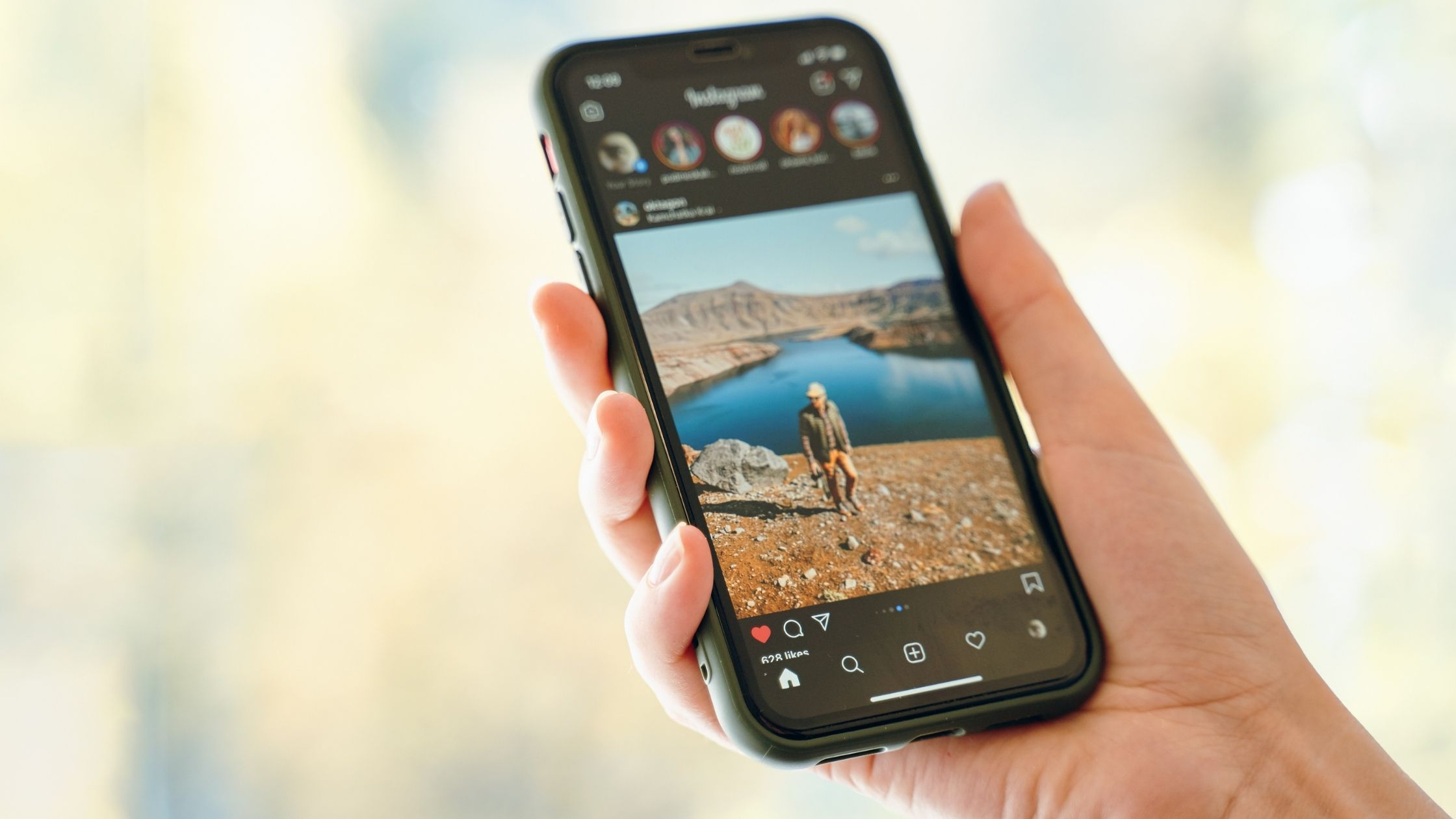 article 'How to run successful instagram ads' It's an image of a hand holding a mobile phone showing the Instagram application with some images visible in the image such as Instagram stories, image of a man walking near the lake, some text and icons inside instagram application