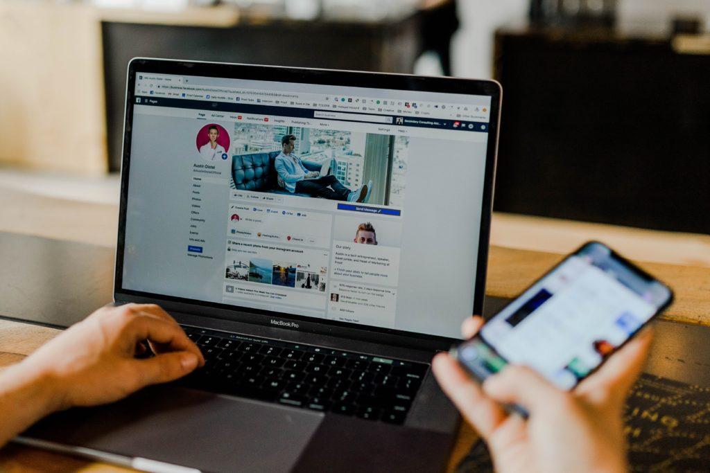 Social-Media-Marketing-Kurs Das Bild zeigt einen Macbook Pro-Laptop, der Social Media, speziell Facebook, auf dem Bildschirm zeigt. Das Bild zeigt, dass eine Person den Laptop verwendet, wobei sich die linke Hand der Person auf der Tastatur des Macbook Pro befindet, während die rechte Hand ein Mobiltelefon hält.