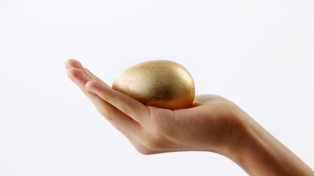 Wie man Reichtum gewinnt Bild zeigt eine Frauenhand, die von der rechten unteren Seite auf weißem Hintergrund kommt und auf ihrer Handfläche ein goldenes Ei hält