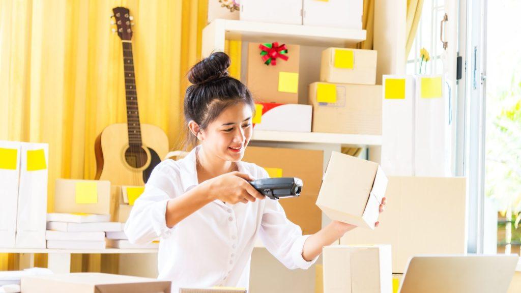 como começar uma imagem de negócio em casa mostra uma mulher na sala pintando um scanner para um pacote como preparação para enviá-lo ou atualizar um sistema, ela está sorrindo e deformando uma camisa branca, o fundo está borrado e mostra uma guitarra e pacotes organizados