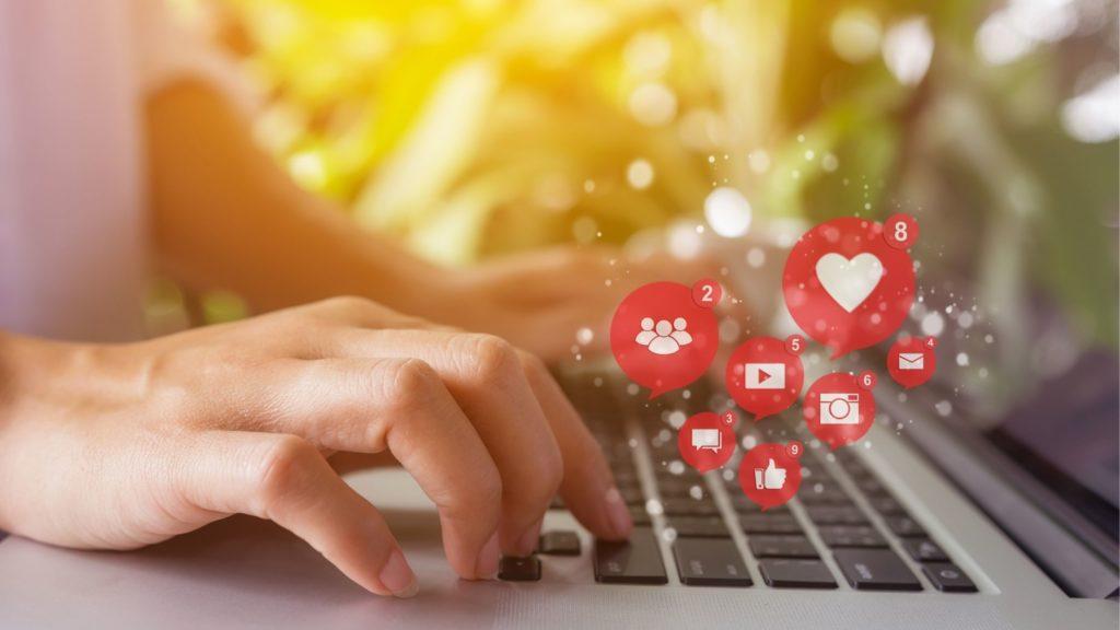 Die Macht des Social-Messaging-Bildes zeigt ein Paar Hände, die an einem Laptop arbeiten, der mehrere Finger auf der Tastatur mit einem verschwommenen Hintergrund mit Pflanzen drückt. Es gibt rote Social-Messaging-Symbole wie Gruppe, Herz, Like, Play, Bild, E-Mail und Chat-Box.
