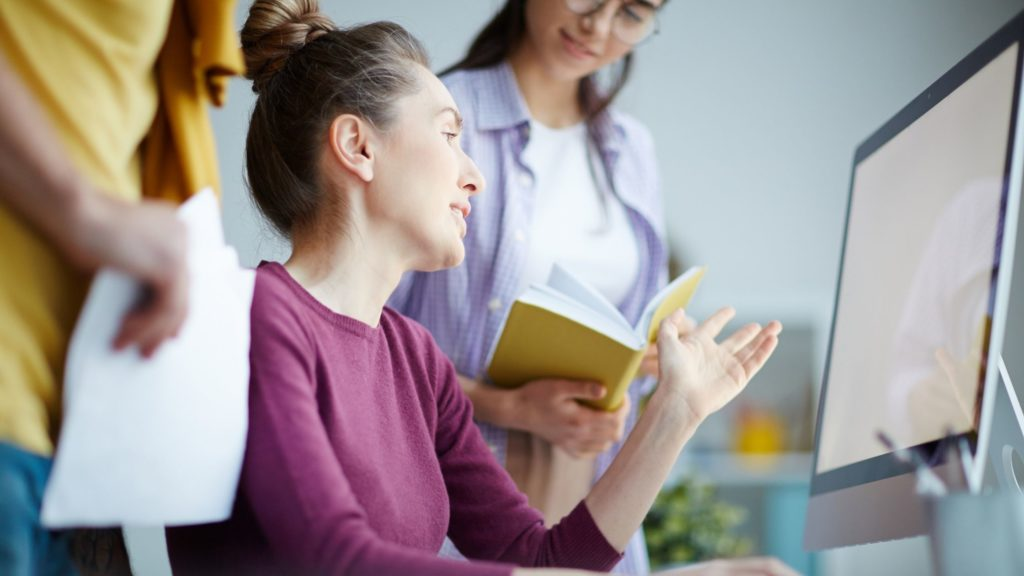 What is a niche marketing image shows 3 people while the two them are girls and the other one is unknown. This is an image of a woman wearing purple long-sleeves sitting in front of her computer while talking to another woman on her left wearing white inner shirt and long-sleeves.
