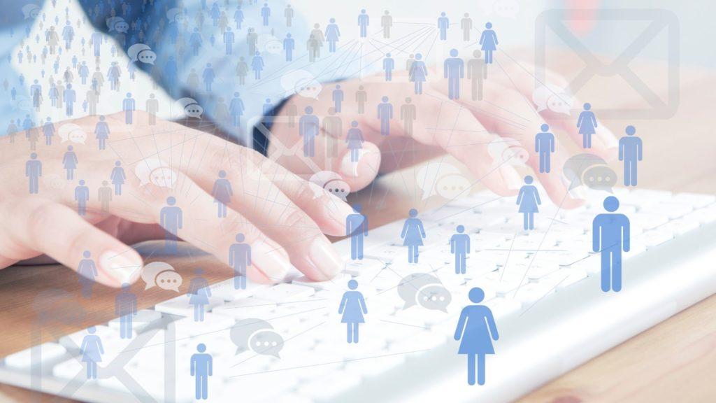 Como fazer anúncios no Facebook Imagem mostra as mãos de uma mulher sobre um teclado de computador e um gráfico de sobreposição de desenho humano azul ligado a linhas e ícone de chat mostrando networking humano saindo no ar.